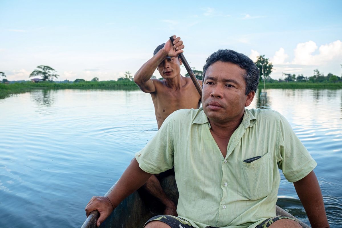 Ko Kyaw Sein Tun with one of his employees rowing boat around his fish pond