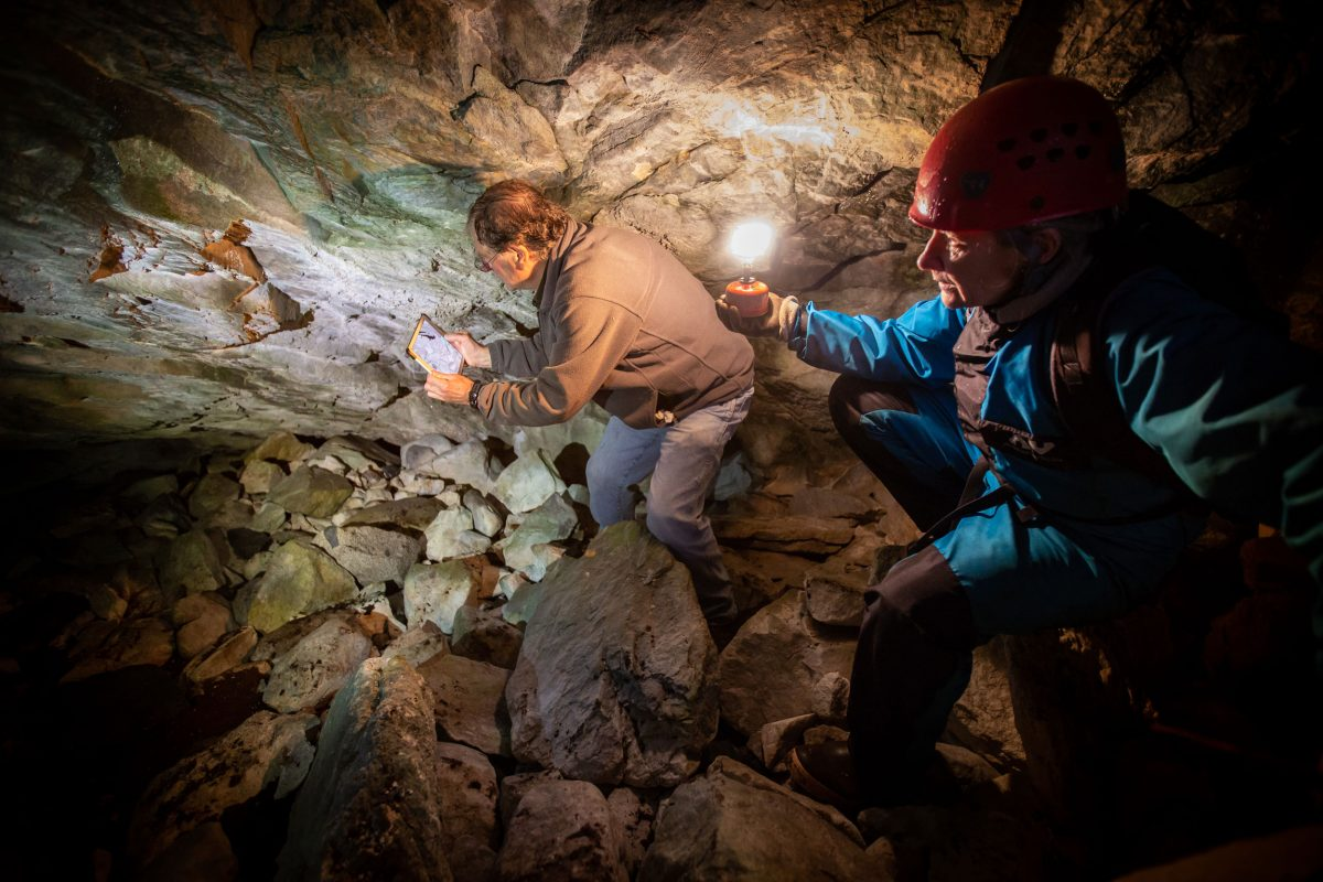 Researchers climb through a cave.