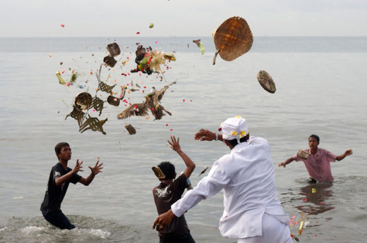 Devotees throw offerings into the ocean as part of a cleansing ritual known as Melasti. Photo by Made Nagi/epa/Corbis