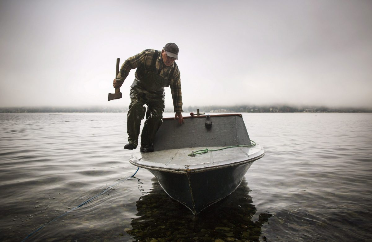 George Moore grabs an ax to salvage a log near Gibsons, British Columbia