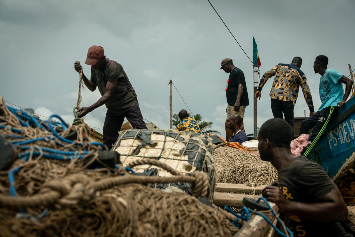 Pangou (left) and his Congolese crew prepare a pirogue to head out to sea.