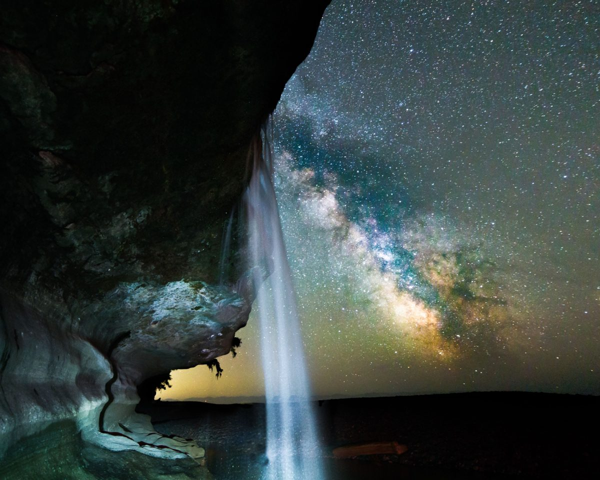 the milky way with a waterfall in the foreground