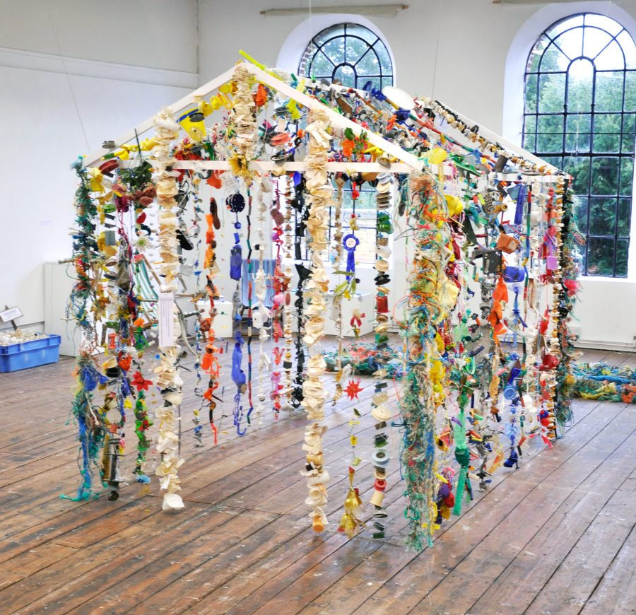 Garlands of unwashed plastic beach debris form the Oil Age Hut installation. Photo courtesy of Fran Crowe
