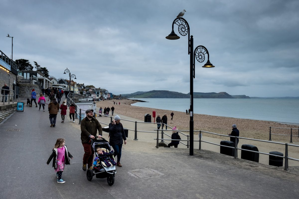 People walk along the seafront past streetlights shaped like ammonites in Lyme Regis. The town was the home of Mary Anning, and is one of the most productive areas of England's Jurassic Coast.