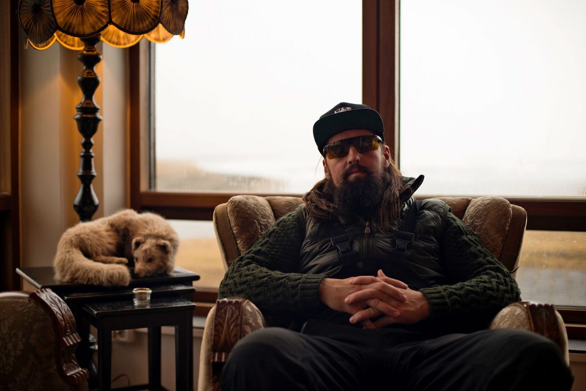 Mink hunter Snorri Rafnsson sits in a chair next to a stuffed mink