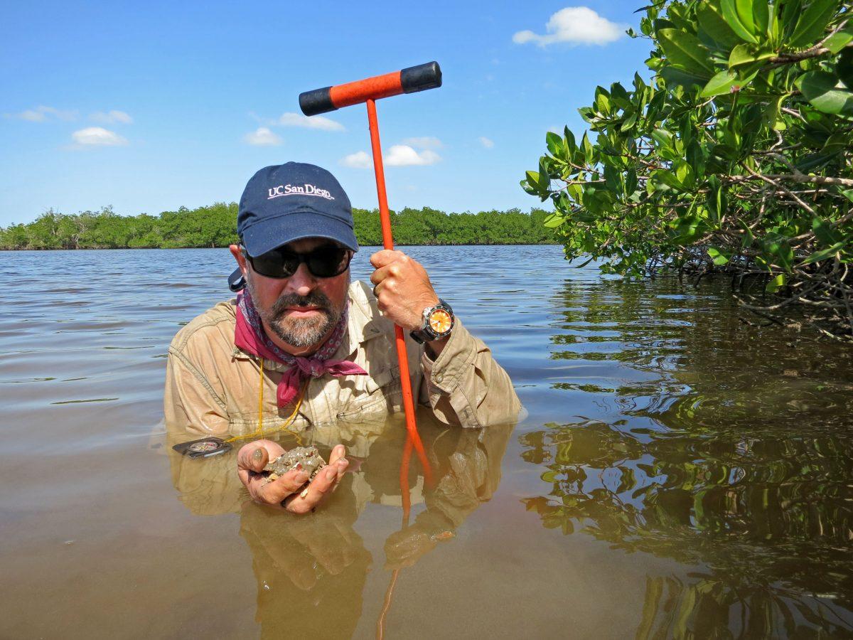 Dominique Rissolo examines sediment for artifacts in the water off Vista Alegre