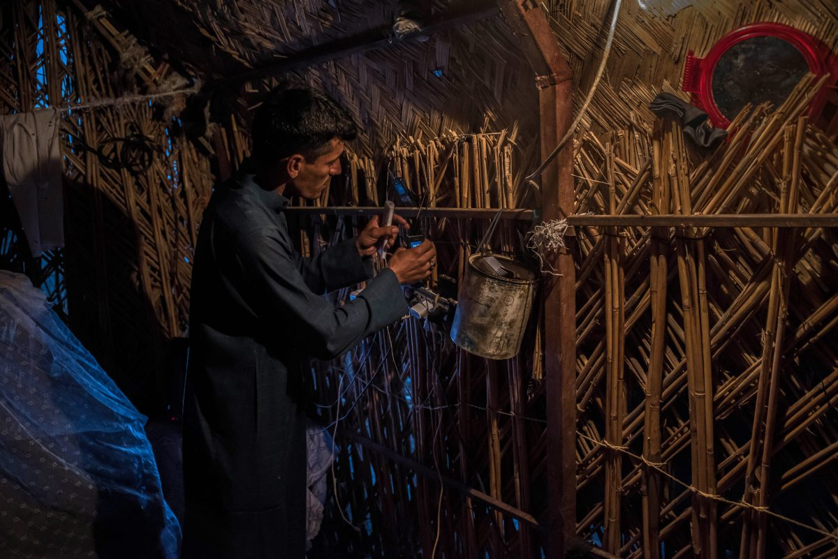 Ali Murad Hassan charges a phone in his reed house in Ishan Gubba, deep in the Central Marsh. He has set up a generator outside his house that provides a few hours of electricity each day. Photo by Emilienne Malfatto