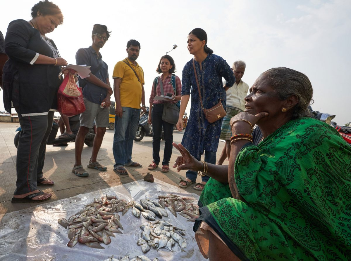 A fish vendor at Marina Beach, in Chennai, India, discusses her offerings with Fishploration participants