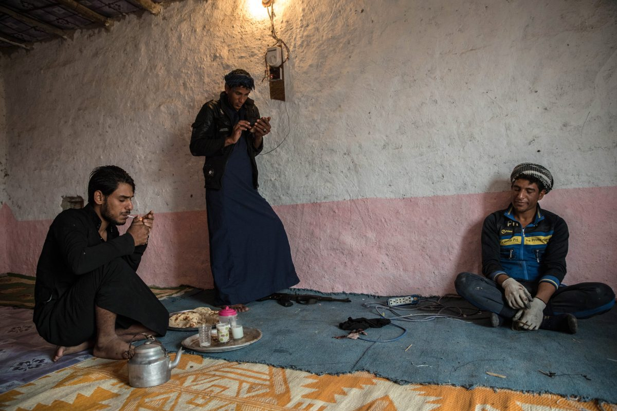 After a breakfast of tea, hot milk, and fresh bread, three buffalo breeders rest inside their home near the Central Marsh, waiting out the rain. Photo by Emilienne Malfatto