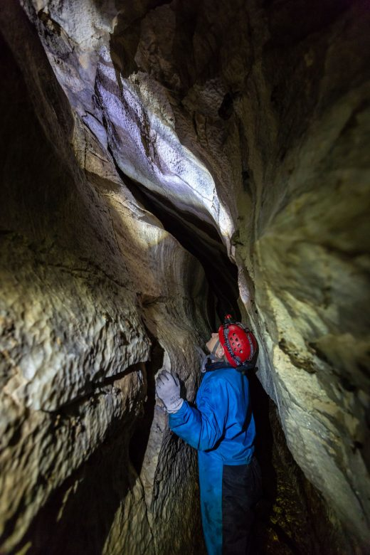 A scientists squeezes through a narrow but tall opening within a cave.