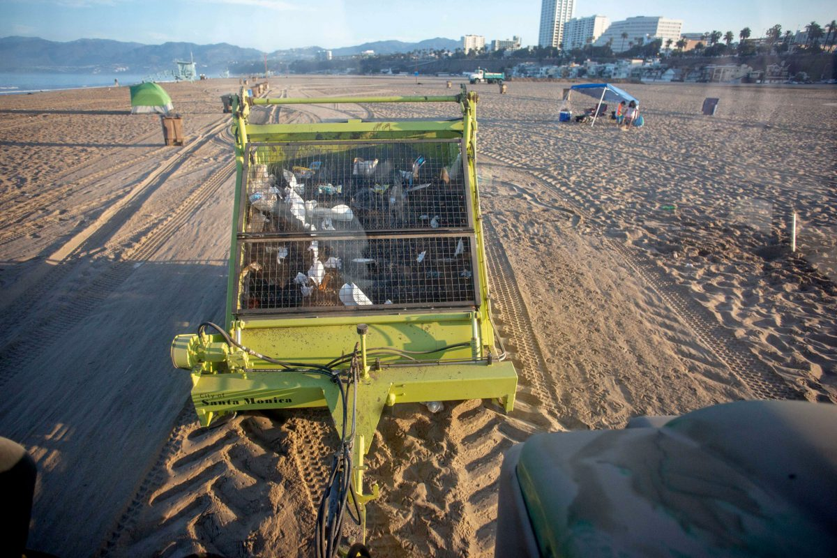 Garbage collecting trailer being towed along Santa Monica Beach by a tractor