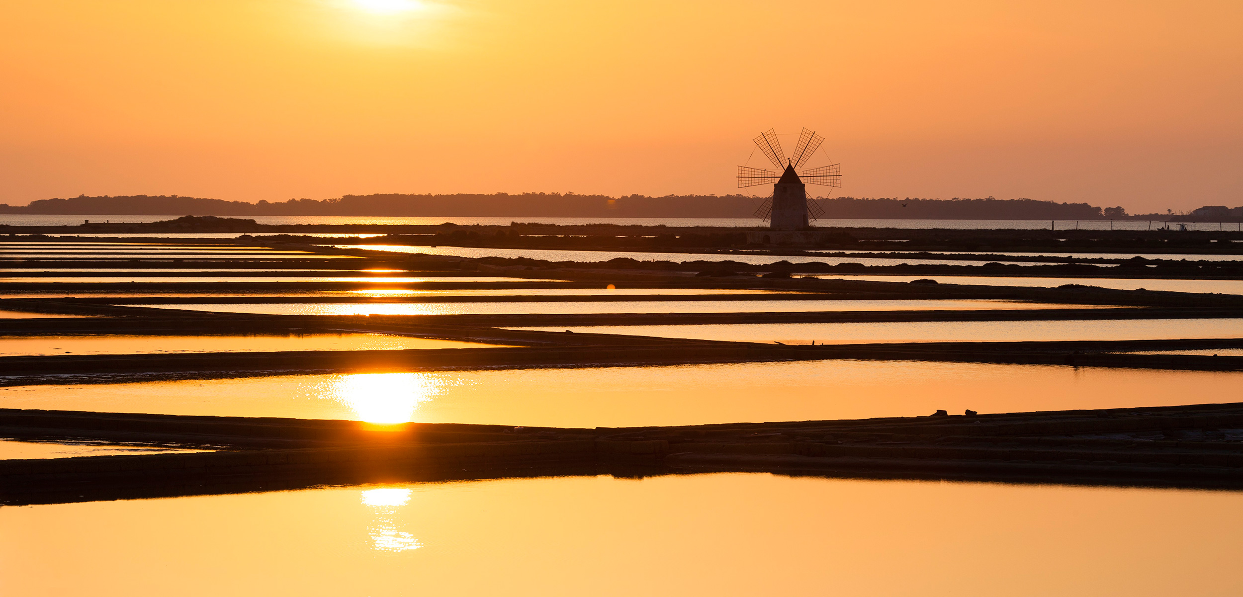 Sunset over the salt flats in Trapani, Sicily. Photo by Frank Lukasseck/Corbis