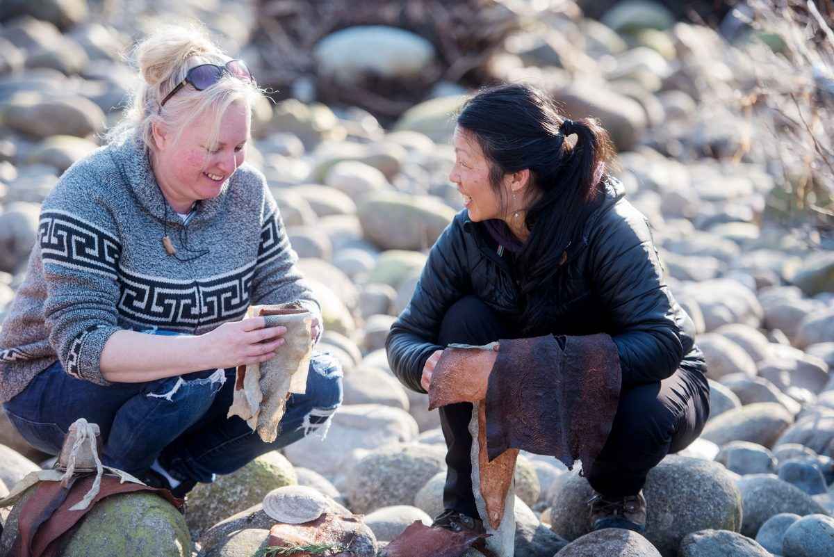 Tracy Williams and Janey Chang process salmon skins along the Seymour River in North Vancouver, British Columbia