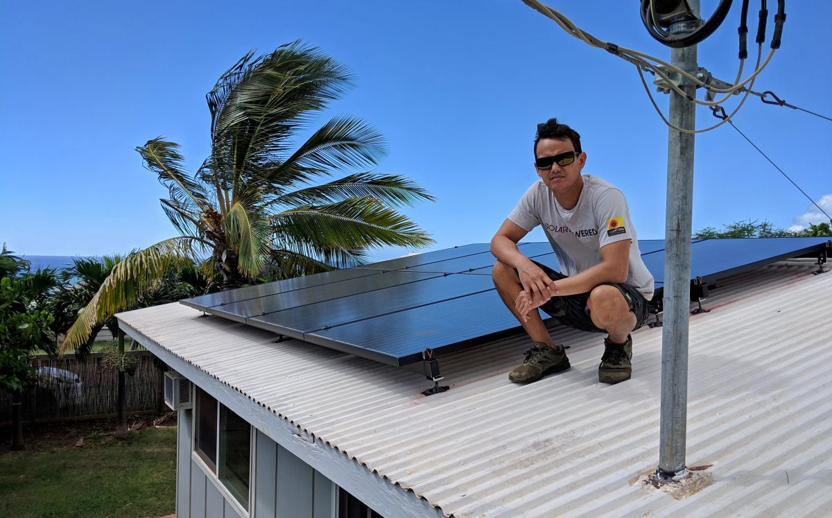 Matt Yamashita on a roof with solar panels